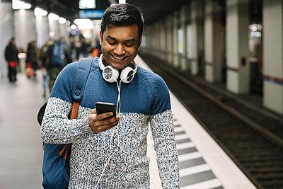 Smiling man using smartphone in subway station - p300m2179984 by Hernandez and Sorokina