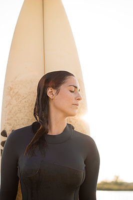 Young woman in wetsuit with surfboard - p552m2002120 by Leander Hopf