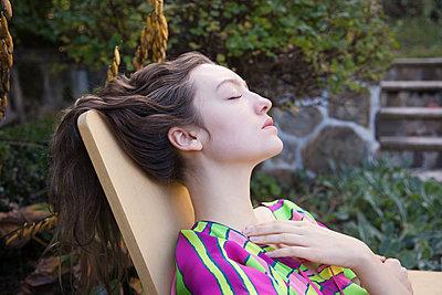 Woman relaxing in lawn chair in backyard - p555m1409423 by Shestock