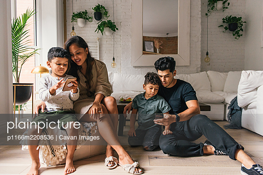 Family together in living room looking at phones and relaxing - p1166m2208536 by Cavan Images