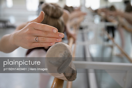 Female ballet dancer with heart-shape ring practicing at barre in dance studio