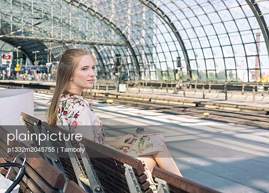 Woman sitting on a bench at the main train station in Berlin - p1332m2045755 by Tamboly
