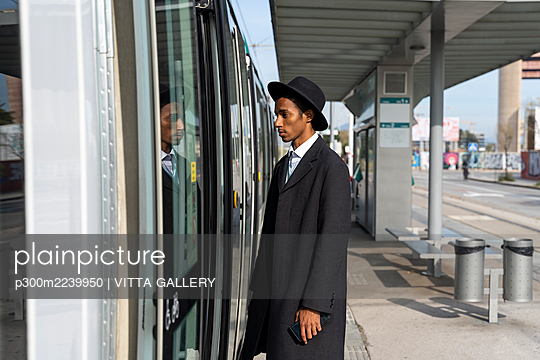 Fashionable young man standing by tram door at station on sunny day - p300m2239950 by VITTA GALLERY