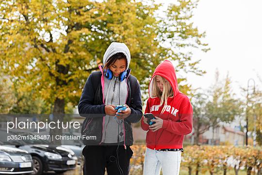 Sweden, Sodermanland, Jarna, Girls (12-13) with hoods on using smart phones
