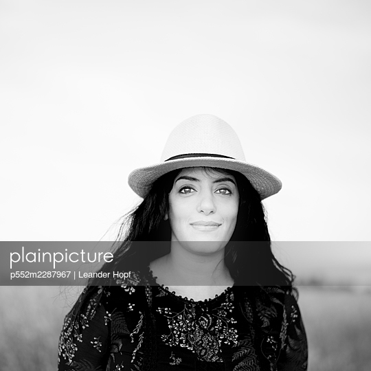 Portrait of black-haired woman with straw hat - p552m2287967 by Leander Hopf