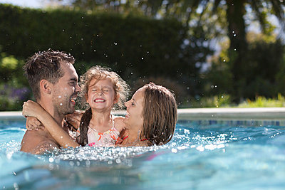 Family playing in swimming pool - p1023m820171f by Paul Bradbury