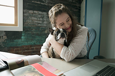 Smiling creative businesswoman hugging dog in lap at desk - p1192m1447488 by Hero Images