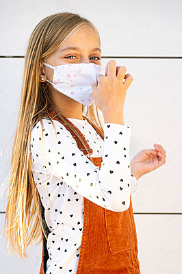 Blond girl wearing protective face mask standing by wall on sunny day - p300m2225887 by Jose Luis CARRASCOSA