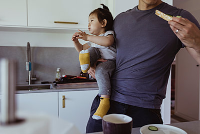 Midsection of father eating food while carrying son in kitchen - p426m2238405 by Maskot