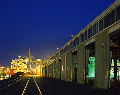 Railroad tracks at harbor at night - p555m1303634 by Tom Paiva Photography