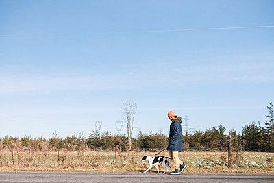 Man walking dog in countryside - p924m2068367 by Viara Mileva
