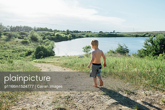 Rear view of shirtless boy walking on field by lake against sky - p1166m1524777 by Cavan Images
