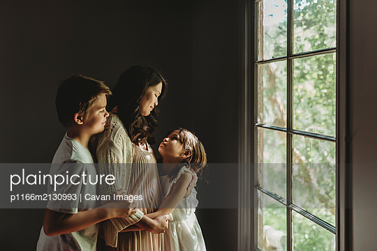 Mother, son, and daughter embrace and look at each other - p1166m2130993 by Cavan Images