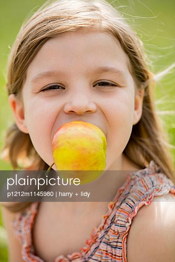 Mädchen isst einen Apfel - p1212m1145980 von harry + lidy