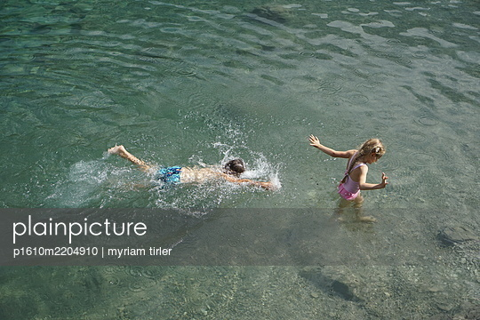 A brother and sister swim and play in a lake  - p1610m2204910 by myriam tirler