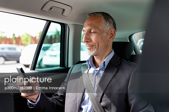 Male professional using smart phone while sitting on back seat in car - p300m2287388 by Emma Innocenti