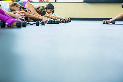 Cropped hand of instructor guiding women in exercising with dumbbells at gym - p1166m1417400 by Cavan Images