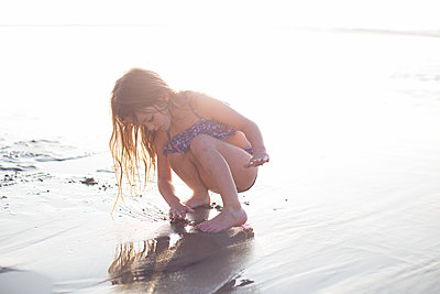 A child independently explores a beach in beautiful light setting. - p1166m2096285 by Cavan Images