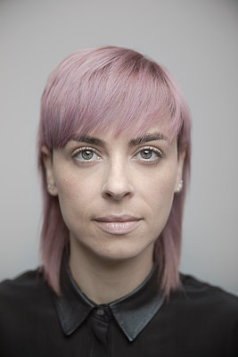 Portrait confident beautiful non-binary gender person with pink hair - p1192m2066228 by Hero Images