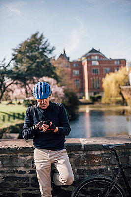Senior man with cycling helmet using smartphone - p300m1580793 von Gustafsson