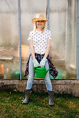Young woman holding green watering can - p300m2103743 von Epiximages