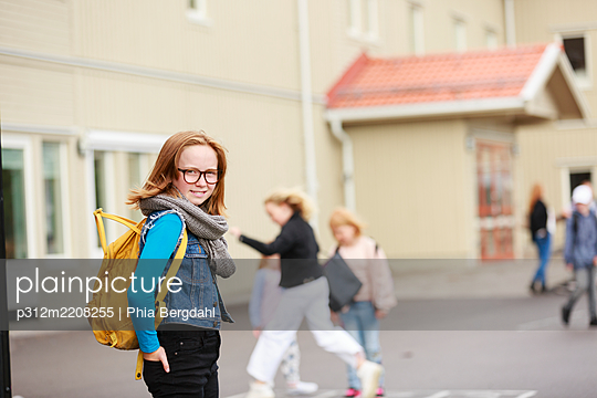 Smiling girl in front of school building - p312m2208255 by Phia Bergdahl