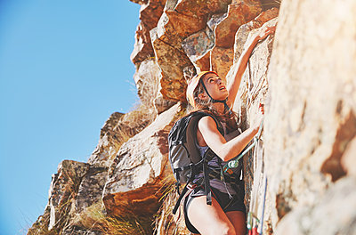 Focused, determined female rock climber scaling rock - p1023m1561188 by Trevor Adeline