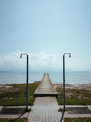 Diminishing perspective of pier over lake against blue sky during sunny day - p1166m2035293 by Cavan Social