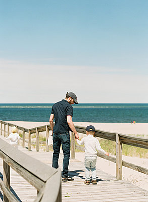 A father holding his son by the hand at the beach - p1166m2200127 by Cavan Images