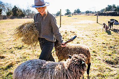 Woman with hay and pitchfork working on farm feeding sheep - p1166m2268907 by Cavan Images