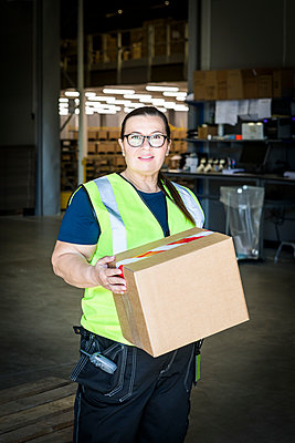 Portrait of confident mature female worker holding cardboard box while standing at distribution warehouse - p426m2018787 by Maskot