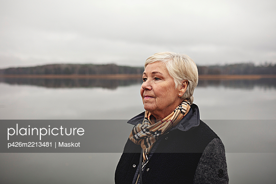 Smiling wrinkled woman looking away by lake against clear sky - p426m2213481 by Maskot