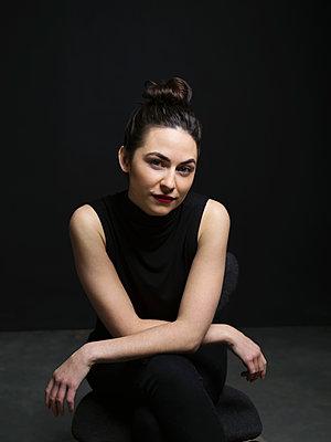 Portrait confident, serious brunette woman against black background - p1192m1403540 by Hero Images