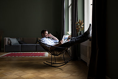 Man relaxing on rocking chair in his living room reading newspaper - p300m1204765 by Rainer Berg