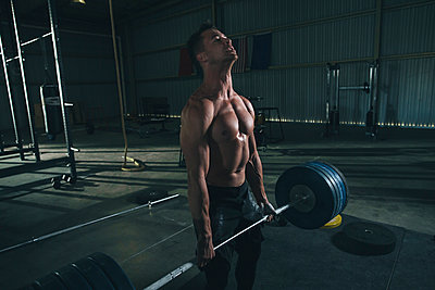 Shirtless male athlete lifting barbell in health club - p1166m1576620 by Cavan Images