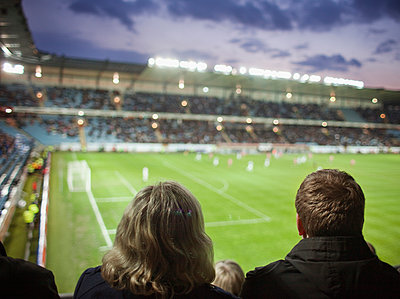 Couple watching a game of soccer together - p1185m1078016f by Adam Haglund