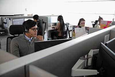 Man with headset working in cubicle at call center - p1192m2040654 by Hero Images
