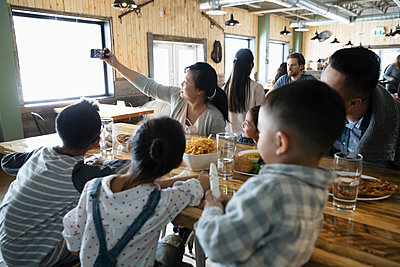 Family with camera phone taking selfie in restaurant - p1192m2088183 by Hero Images