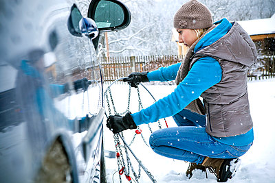 Frau legt Schneekette an, Steiermark, Österreich - p1316m1160672 von Harald Eisenberger
