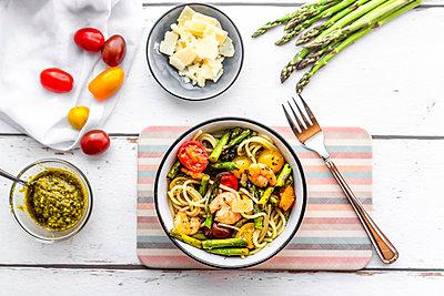 spaghetti with shrimps, green asparagus, tomato, pesto and parmesan - p300m2004411 von Sandra Roesch