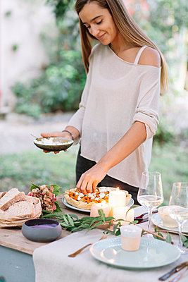 Woman preparing a romantic candelight meal outdoors - p300m2068795 by Alberto Bogo