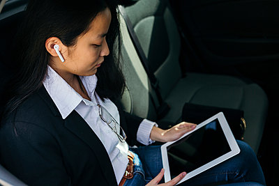 Young businesswoman sitting in car using earpods and digital tablet - p300m2189612 by Xavier Lorenzo