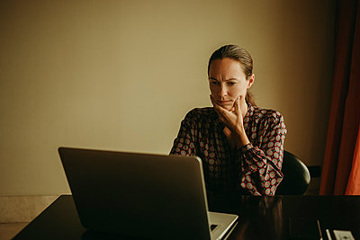 Serious businesswoman working on laptop in office - p300m2220639 by David Molina Grande