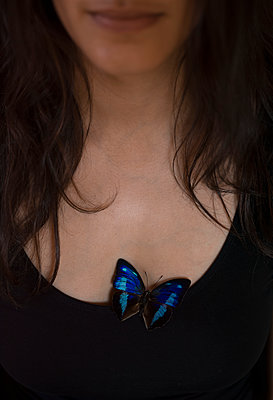 Blue butterfly on t-shirt of young woman - p552m1468183 by Leander Hopf