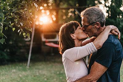 Reifes Paar küsst sich im Garten - p586m1178620 von Kniel Synnatzschke