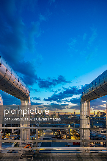 Sunset as viewed through pipe in a refinery - p1166m2131167 by Cavan Images
