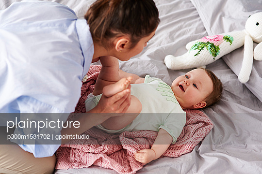 Mother and baby playing on bed at home - p300m1581702 von gpointstudio