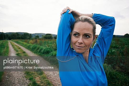 Blonde Frau in Trainingskleidung dehnt sich - p586m971670 von Kniel Synnatzschke