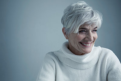 Portrait smiling Caucasian senior woman with short white hair looking away - p1192m1213197 by Hero Images