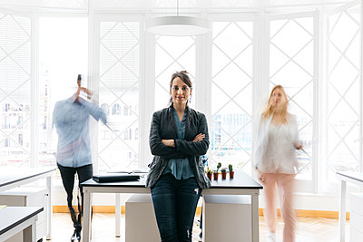 Young businesswoman standing with arms crossed in office while colleagues are moving - p300m1460544 by Josep Rovirosa